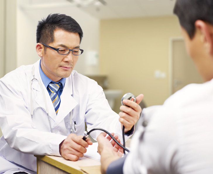 doctor checking his patient blood pressure